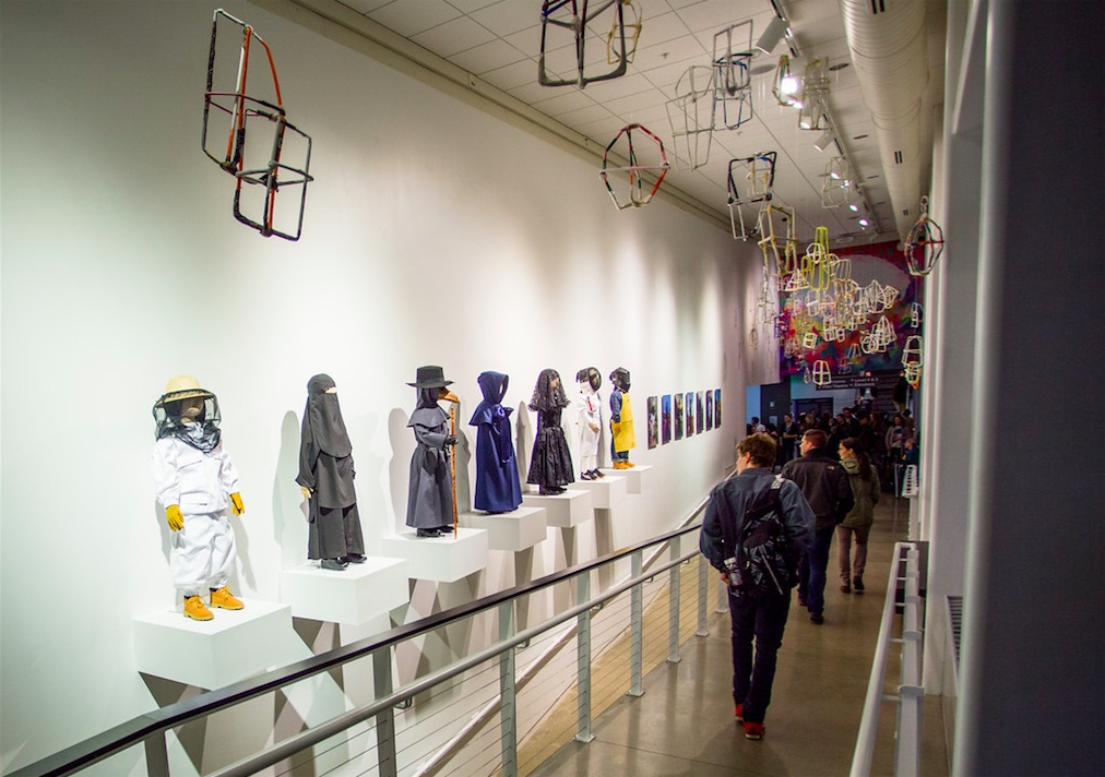 "(above) Jeremy Burleson, Lamps, 2007-2010, Paper, Dimensions variable; (along wall); Laura Swanson, Uniforms, 2015 (""Beekeeper,"" ""Burqa,"" ""Plague Doctor,"" ""Shaker,"" ""Mourning,"" ""Welder,"" and ""Fencer"") Altered garments on ready-made mannequins 4' tall each"