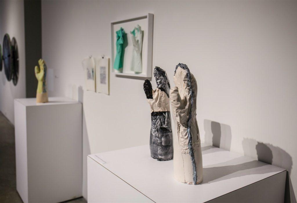 "Funda Susamoglu, Handmade, 2013, Mixed media installation (ceramics, rubber gloves, paper), each ceramic piece is 16 x 6 x 4.7"""